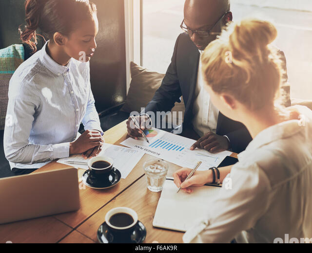 Business people discussing the charts and graphs showing the results of their successful teamwork, multi ethnic - Stock Image