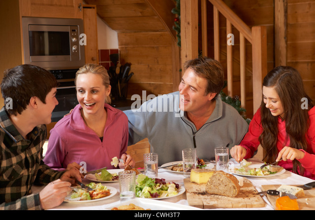 Teenage Family Enjoying Meal In Alpine Chalet Together - Stock Image