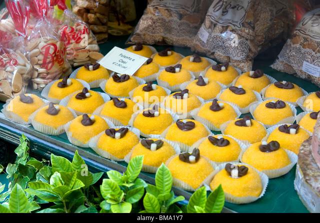 colourful yellow cakes in bakery window, bergamo, italy - Stock Image