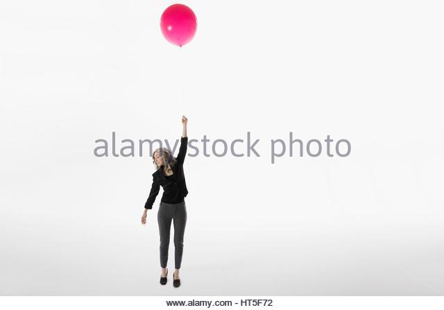 Woman holding red balloon, floating against white background - Stock-Bilder