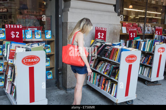 Young blond woman shopping for books at The Strand bookstore in New York City - Stock Image
