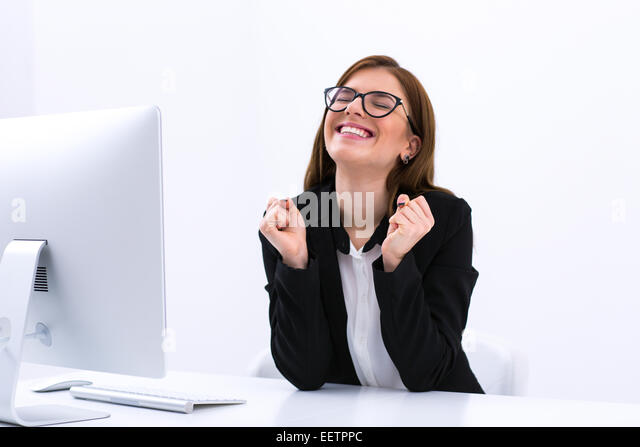 Successful business woman sitting at her workplace in office - Stock Image