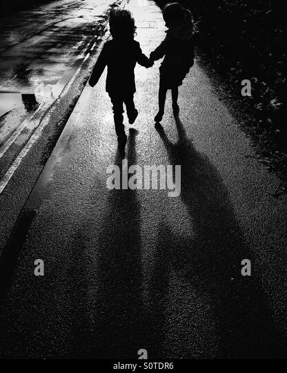 Silhouette of two children holding hands - Stock Image