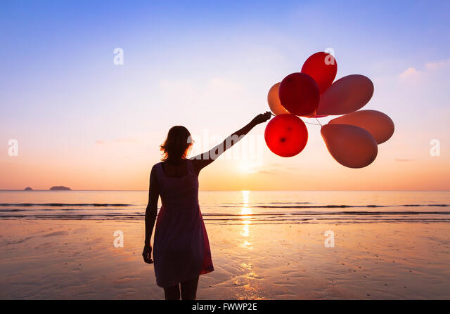 imagination and creativity, girl with multicolored balloons at sunset with copyspace, inspiration concept - Stock Image