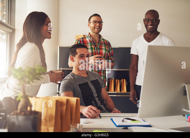 Diverse group of four Black, Hispanic and Caucasian young adult entrepreneurs together in front of computer monitor - Stock Image