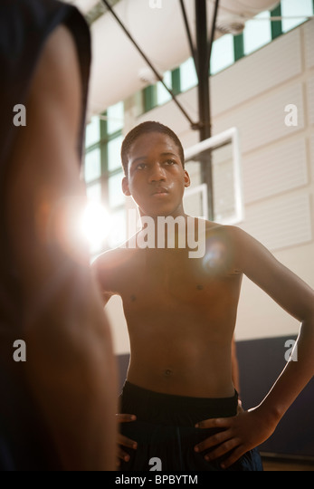 African american youth in a sunlit gym with shirts off playing basketball with shallow depth of field focus - Stock Image