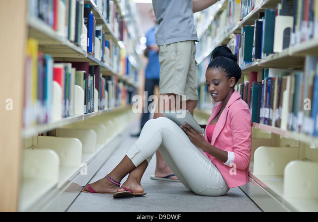 Female student sitting on floor in library using digital tablet - Stock Image