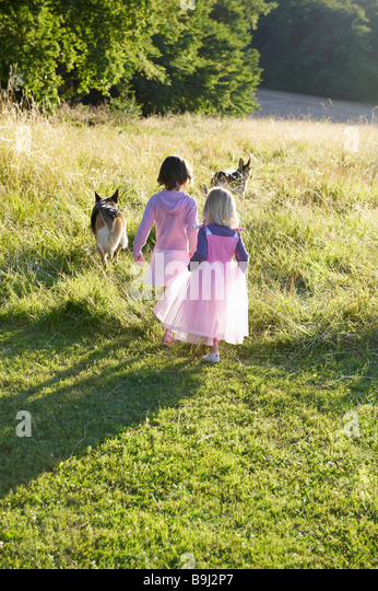 Girls dressed as princesses,  with dogs - Stock Image