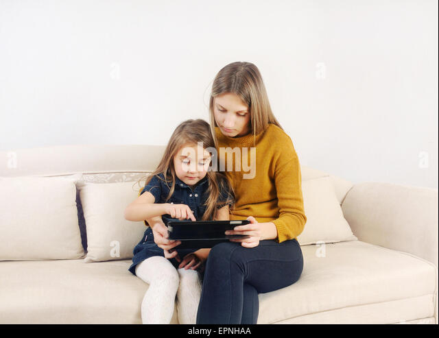 little girl with her mother using tablet device on the sofa at home, happy family, technology concept - Stock Image