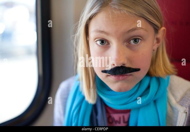 Ten year old girl wears a mustache. - Stock Image