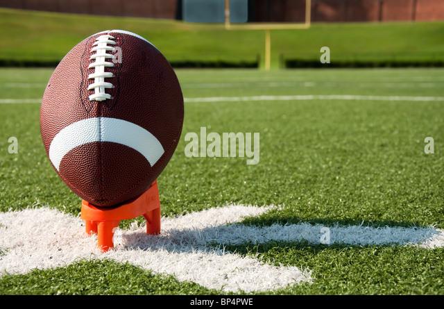 American Football on Kicking Tee on Field - Stock Image