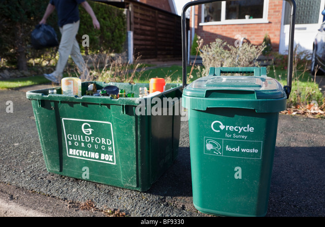 Green kerbside recycling boxes for glass and food waste waiting for collection outside a house. Surrey England UK - Stock Image