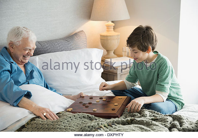 Grandfather and grandson playing checkers in bedroom - Stock Image