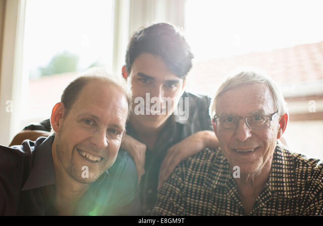 Portrait of three generation family smiling together at home - Stock Image