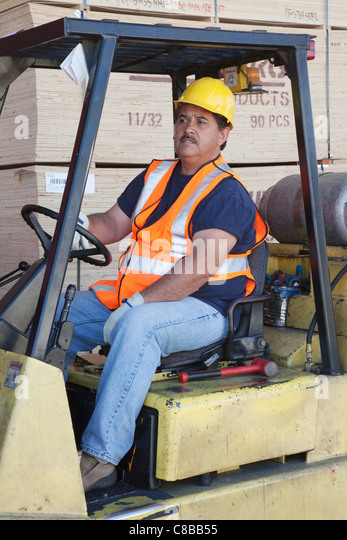 Forklift driver driving in warehouse - Stock Image