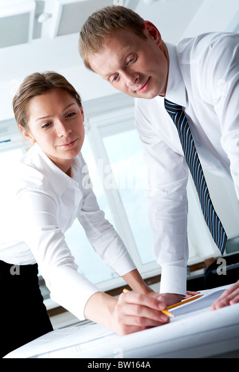 Portrait of busy companions drawing construction plan at meeting - Stock Image