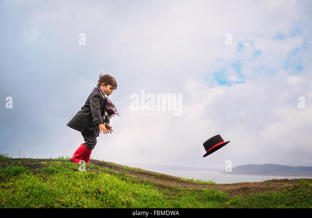 Boy chasing his hat blowing away in the wind - Stock Image