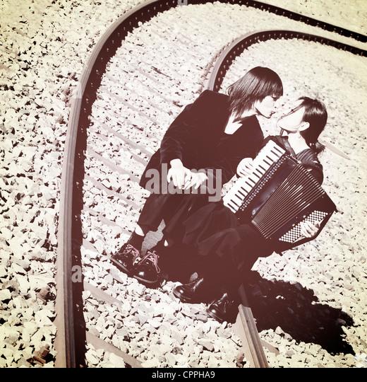 a vagabond couple sitting on railroad tracks and kisses - Stock Image