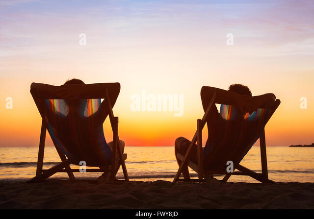 enjoy life concept, couple relaxing in beach hotel  at sunset, happy people on honeymoon, paradise travel destination - Stock Image