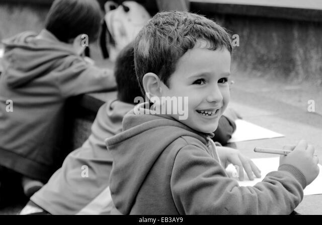 China, Hong Kong Island, Hong Kong, Boy (4-5) smiling while drawing, people in background - Stock-Bilder