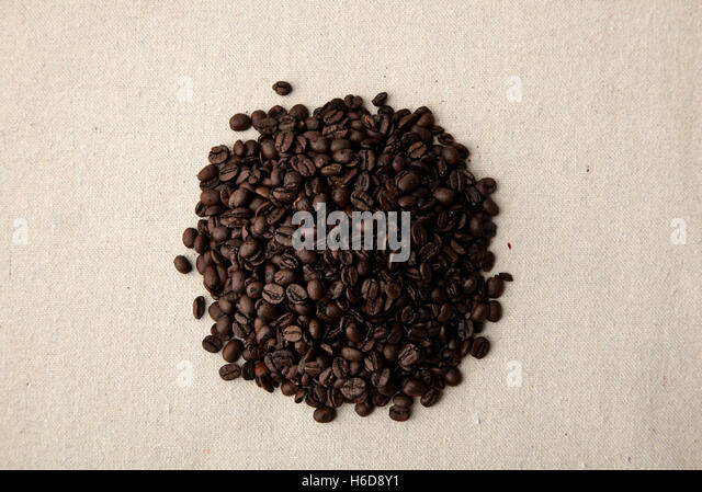 Small pile of coffee beans on linen - Stock Image