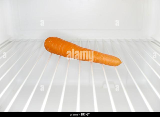 Single carrot sitting on shelf inside refrigerator - Stock Image