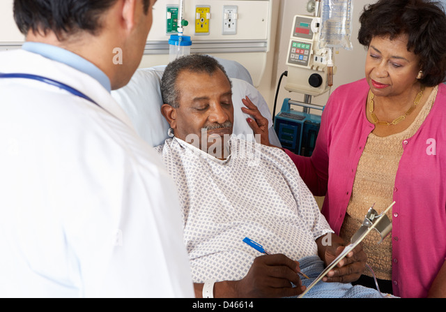 Doctor Explaining Consent Form To Senior Patient - Stock Image