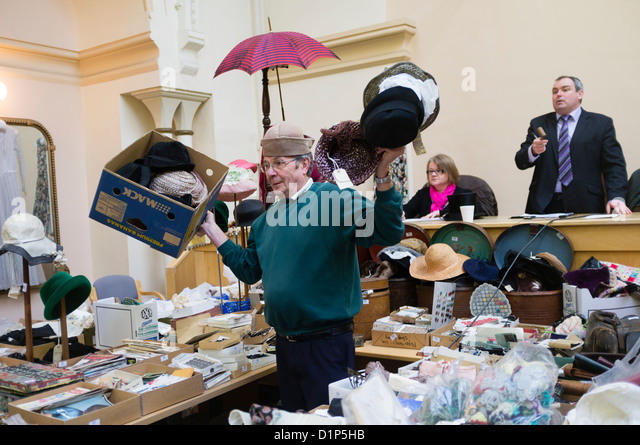 An assistant holding up hats on sale at an auction of antiques, clothes and bric-a-brac, UK - Stock Image