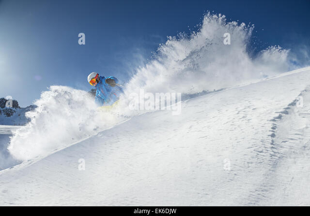 Skier skiing downhill in high mountains during sunny day. - Stock-Bilder