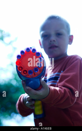 5 year old boy pointing toy gun - Stock Image