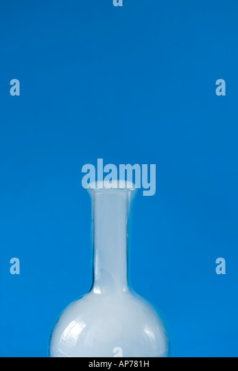 simple round bottom flask with smoke dry ice reaction and blue background vertical room for type - Stock Image