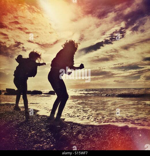 Children playing dare with tide on beach - Stock-Bilder
