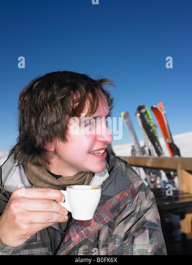 Man drinking hot drink at ski resort - Stock-Bilder