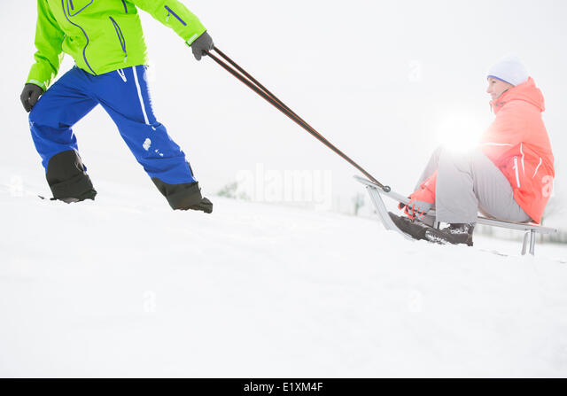 Low section of man giving sled ride to woman in snow - Stock Image