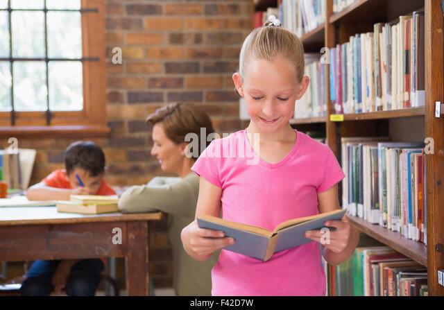 Cute pupil reading in library - Stock Image