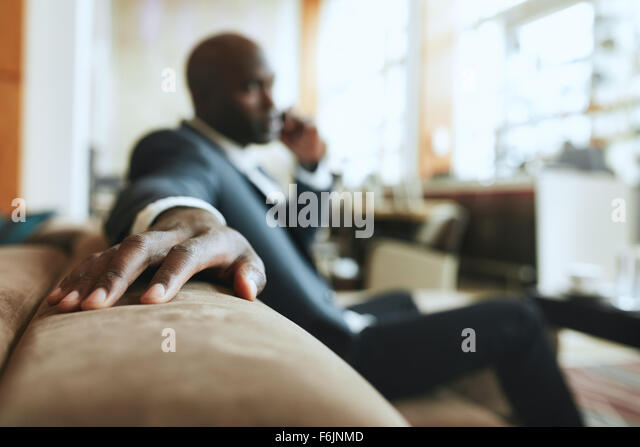 African businessman sitting in lounge area at hotel reception talking on mobile phone, focus on hand. - Stock-Bilder