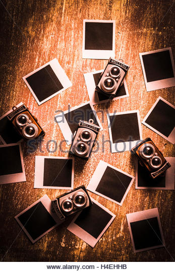 Photographic nostalgia in the taking with a bunch of old vintage camera toys surrounded by a abstract vintage photo - Stock Image