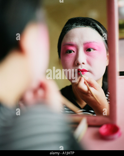 Rear view of a young woman applying lip liner - Stock Image