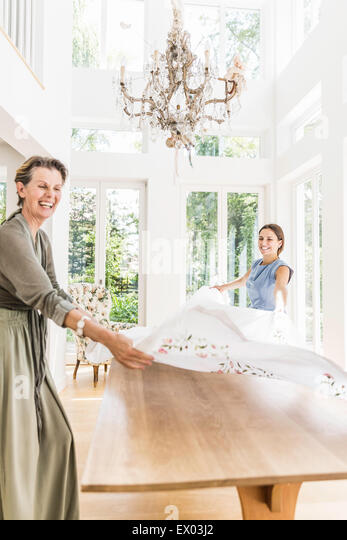 Young woman and mother throwing tablecloth onto dining room table - Stock Image