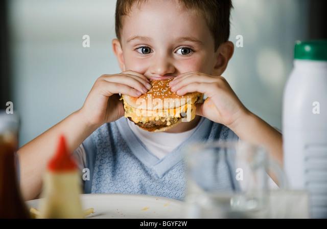Little boy eating cheeseburger - Stock-Bilder