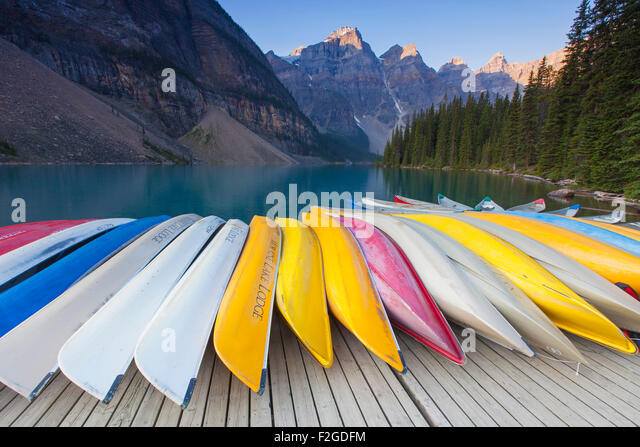 Colourful canoes at Moraine Lake in the Valley of the Ten Peaks, Banff National Park, Alberta, Canada - Stock Image