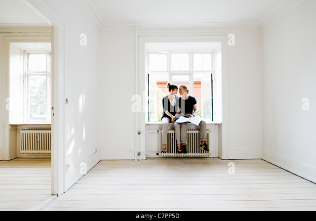 Couple sitting in window of new home - Stock Image