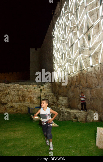 Israel. Kids playing near the 'Arabesque' light sculpture at Jerusalem's old city wall, during the June - Stock Image