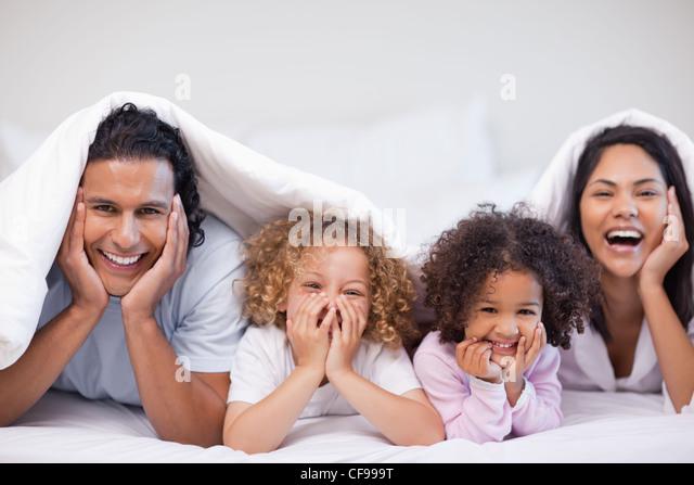 Joyful family hiding under the blanket - Stock Image