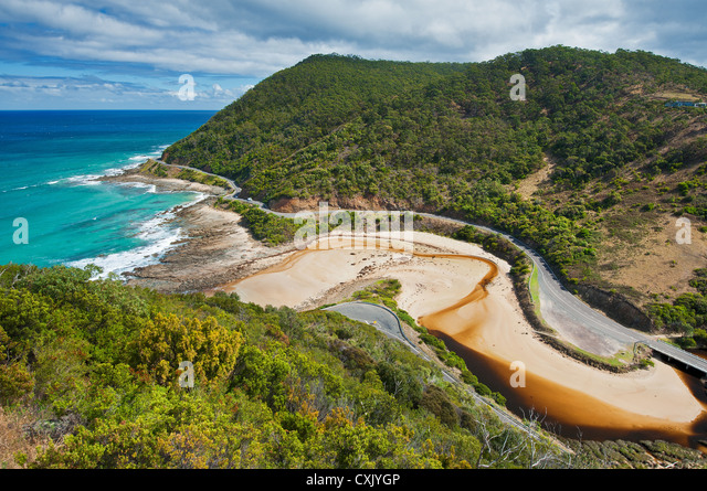 The Great Ocean Road winding its way along the coastline. - Stock Image