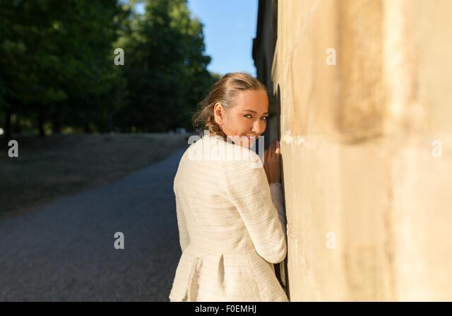 Young shy woman smiling from back into camera - Stock Image