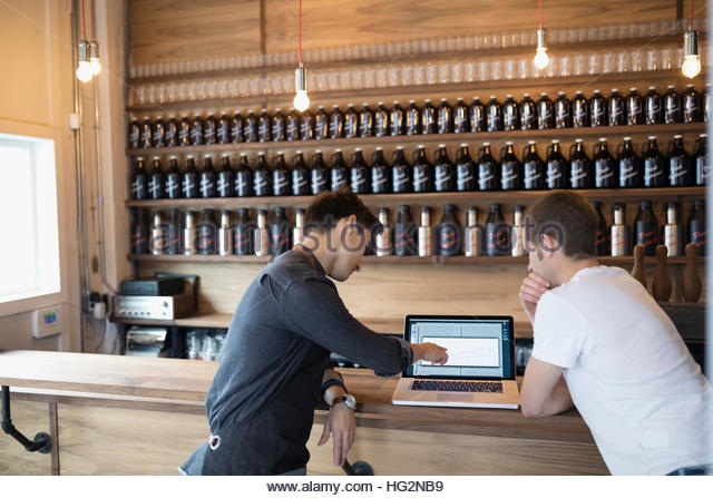 Male brewers working at laptop in brewery tasting room - Stock Image