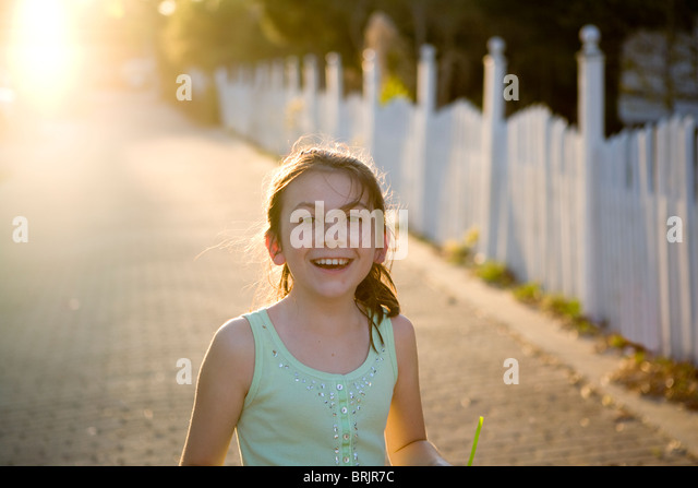 A freckled girl is smiling with a picket fence and sun in the background. - Stock Image