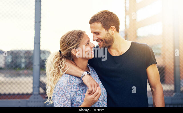 Couple looking into each others eyes while smiling - Stock Image
