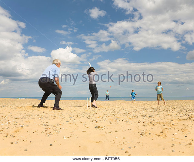 People playing Cricket on a beach - Stock Image